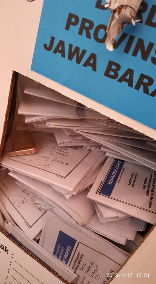 sebuah smartphone bercampur tumpukan surat suara